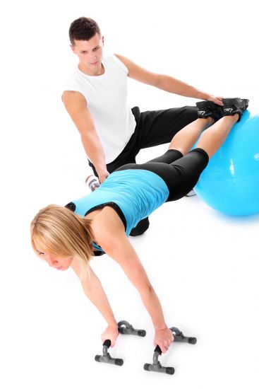 A picture of a young woman working out with her personal trainer