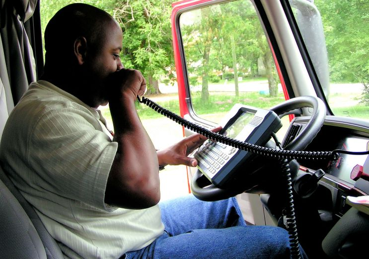 African American Truck Driver Using A Onboard Computer And CB Ra