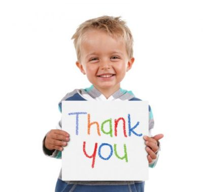 Child holding a crayon thank you sign standing against white bac