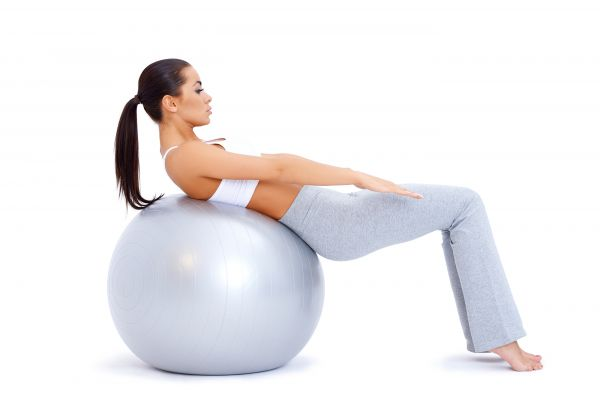 Cute woman doing abdominal muscles with fitness ball